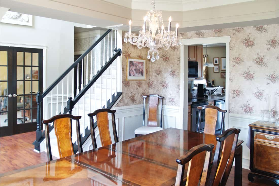 Dining room with classic vintage chicwallpaper design, long wood table, candle and crystal chandelier