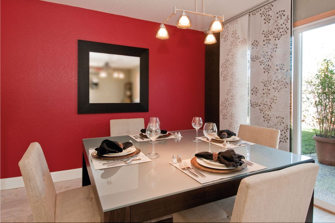 dining room with a single framed mirror on a crimson red wall