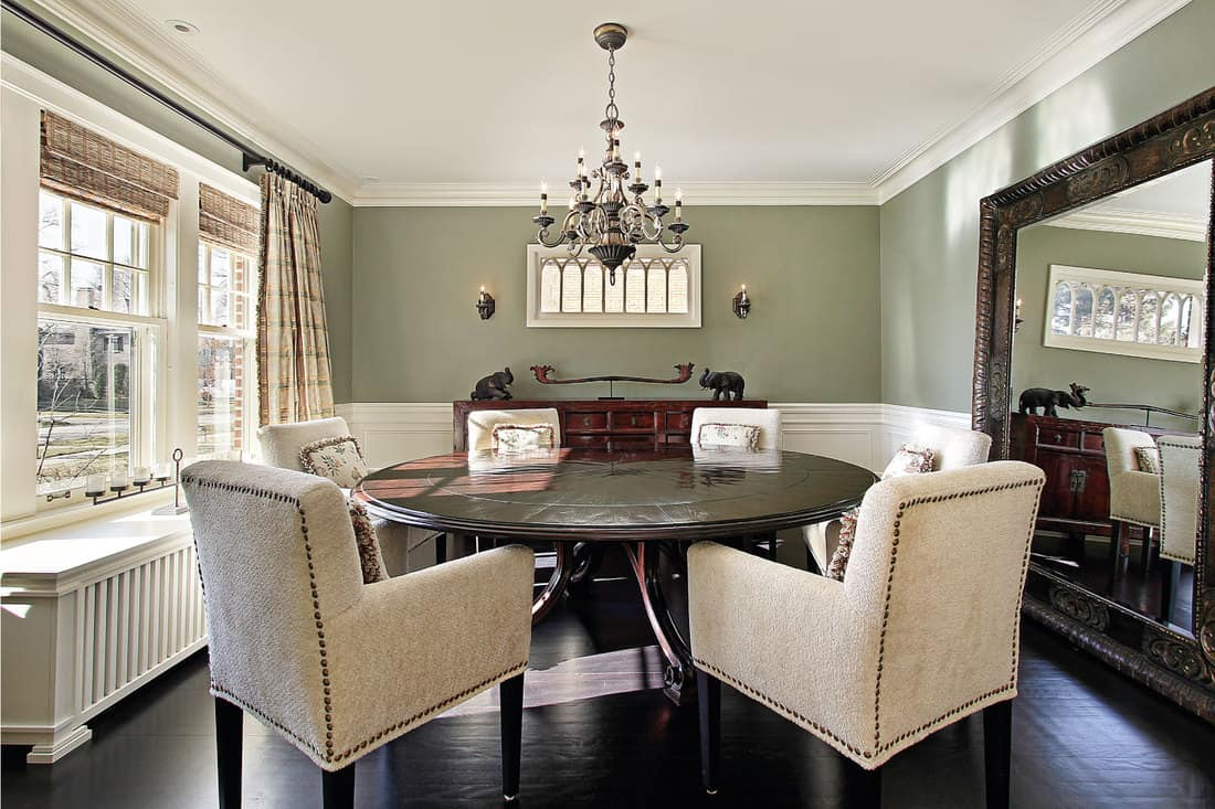 dining room with olive colored walls, armchairs, wooden round table, wall sized mirror for a small room