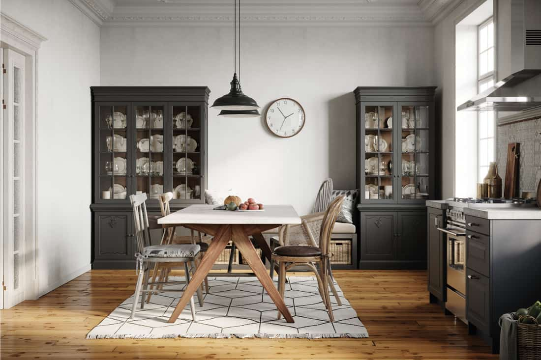 Small kitchen with crockery cabinets at the back and a dining table in center on rug