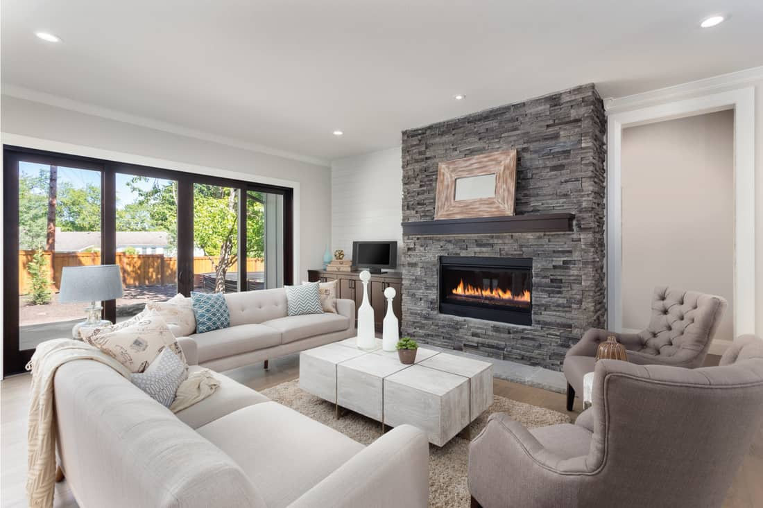 Furnished living room in newly constructed luxury home with furniture facing the fireplace