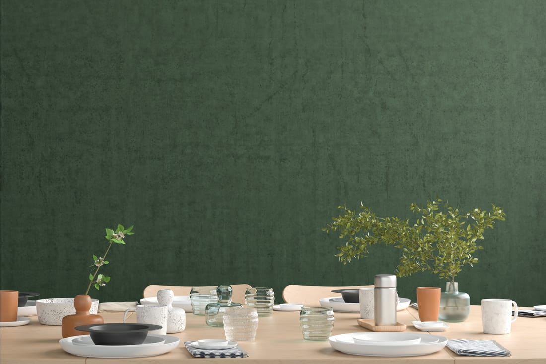 Green solid color textured wallpaper in a dining room with table and utensils