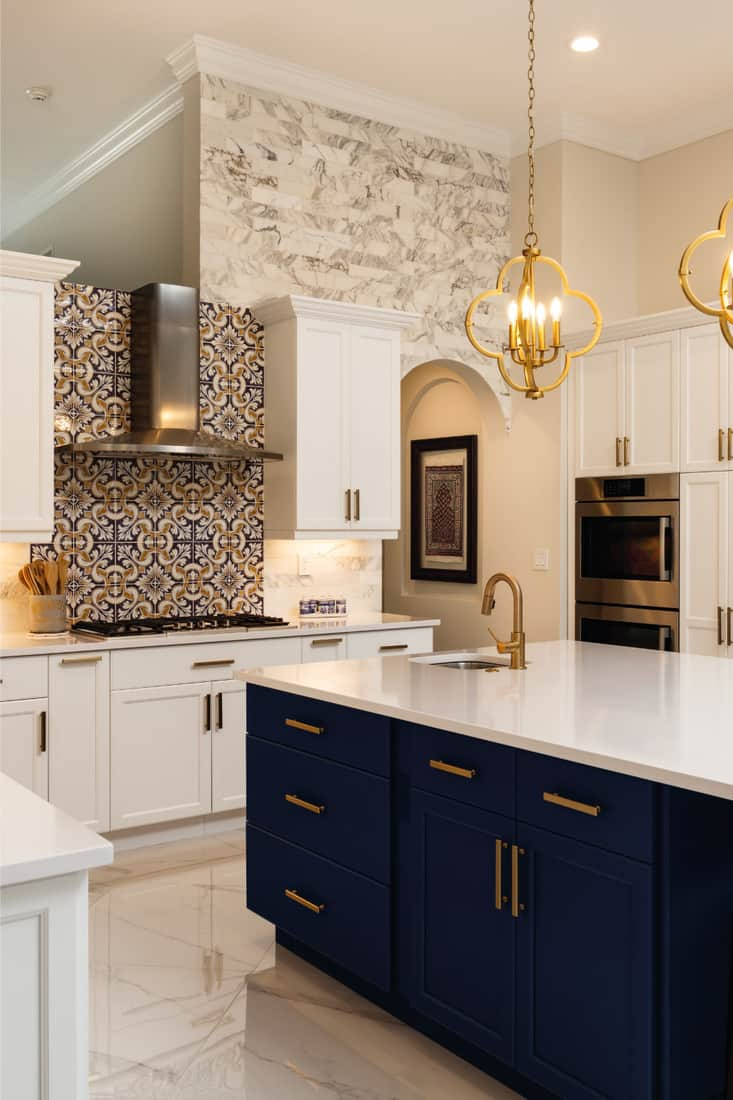 Home kitchen with white cabinets, navy blue and gold island table with white countertop