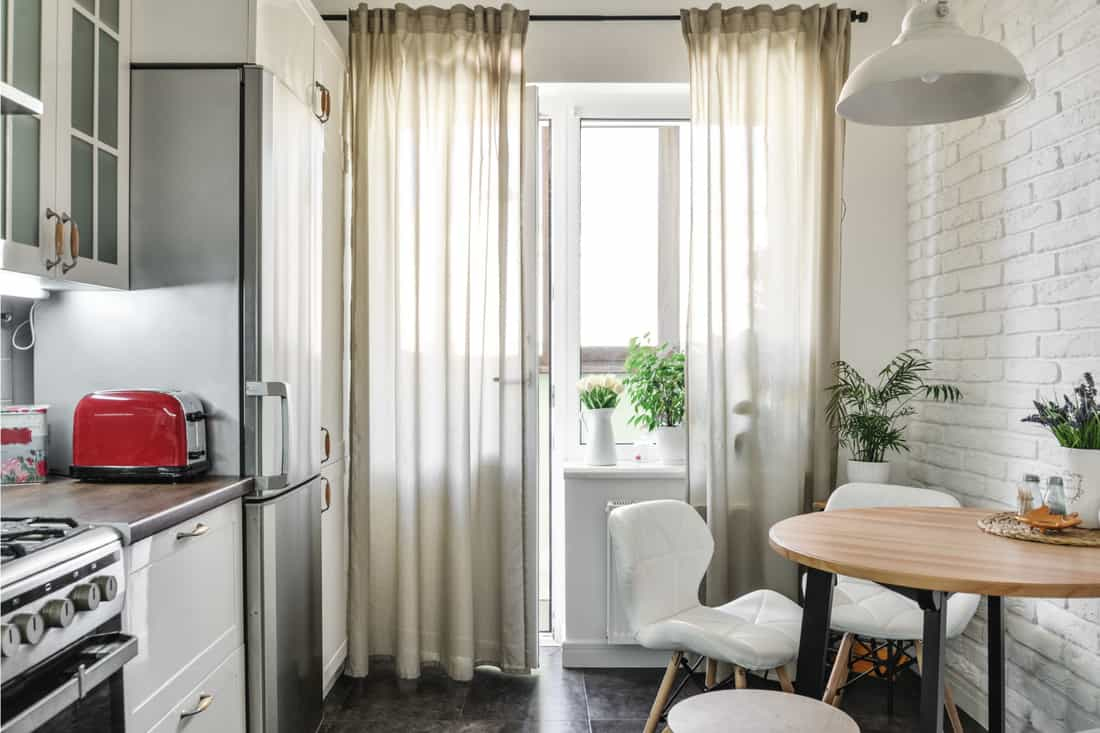 Kitchen in Scandinavian style with white furniture and long floor to ceiling curtains