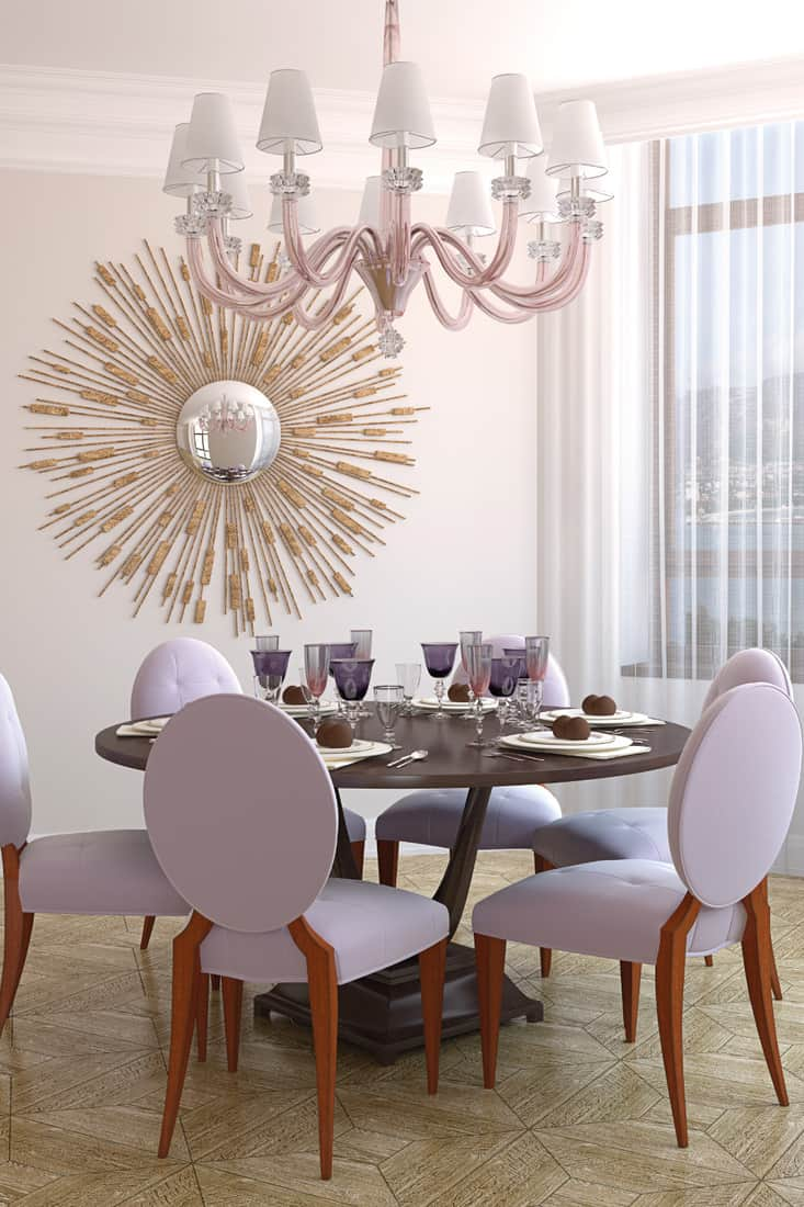 light purple walled dining room with chandelier and sunburst mirror