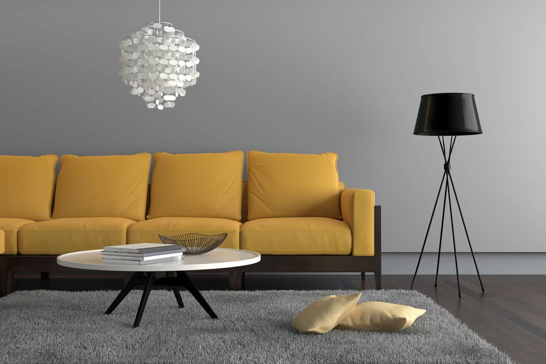 living room showing a yellow sofa, with a lamp, ornate pendant and a table with decoration. There is a gray carpet with two pillows on it. Gray wall surrounding the scene with wooden floor