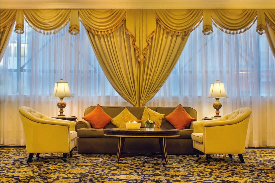 Living room with furniture, ornate curtains and carpet in mustard yellow