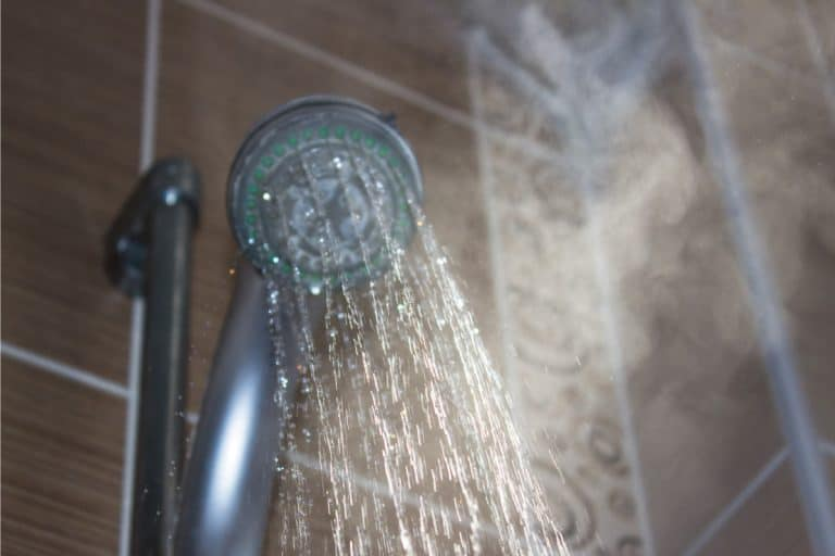 Low angle view of steaming water flowing from shower head in the bathroom, How Big Should A Steam Shower Be?