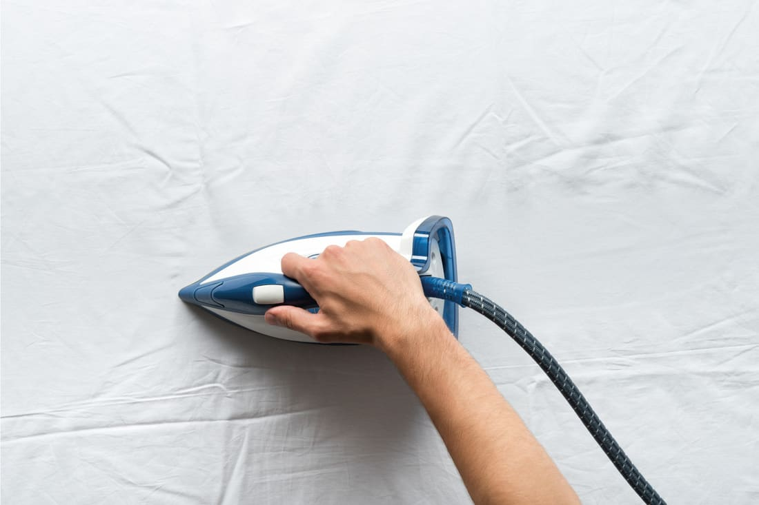 Man ironing wrinkles on white bed sheets