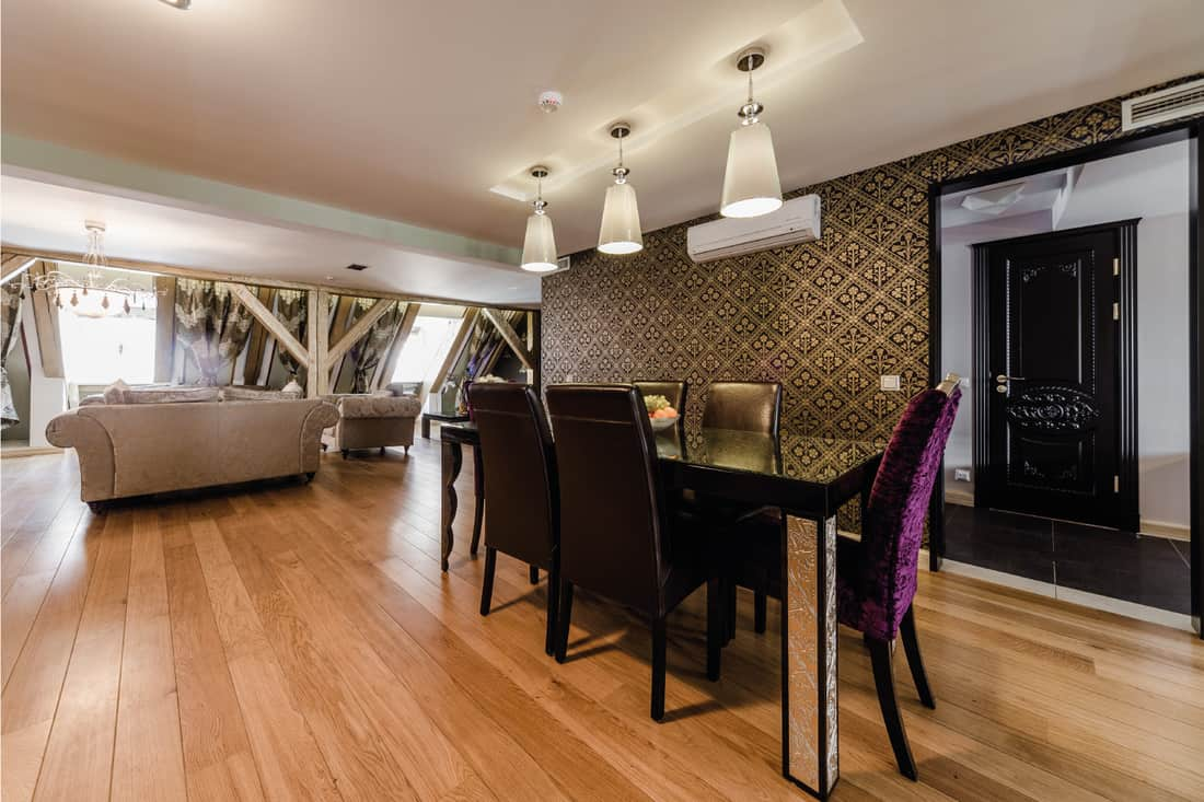 Modern dining room with luxe art deco pattern wallpaper, pendant lights and wooden floor