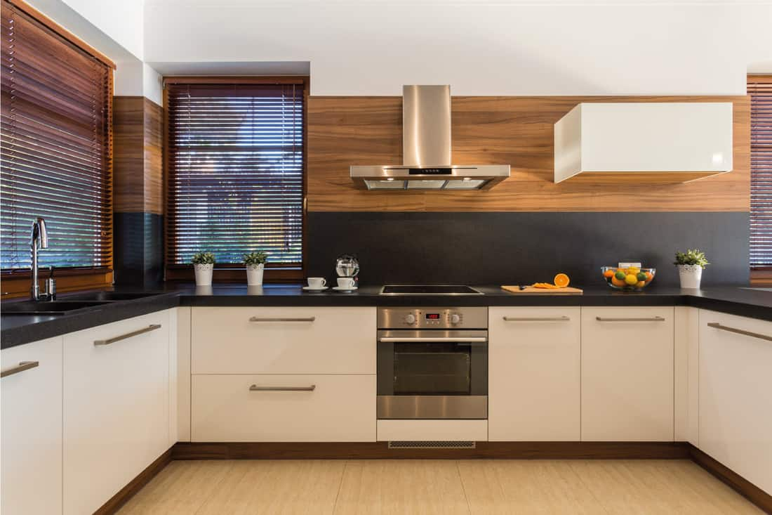 Modern furniture in luxury kitchen with wooden blinds on the windows, black granite countertop and white cabinets