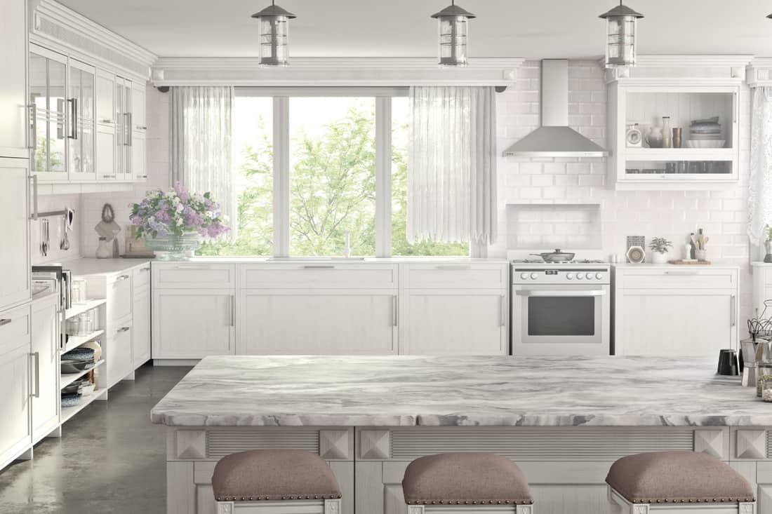 Modern kitchen with light dainty curtains and marble table and counter tops