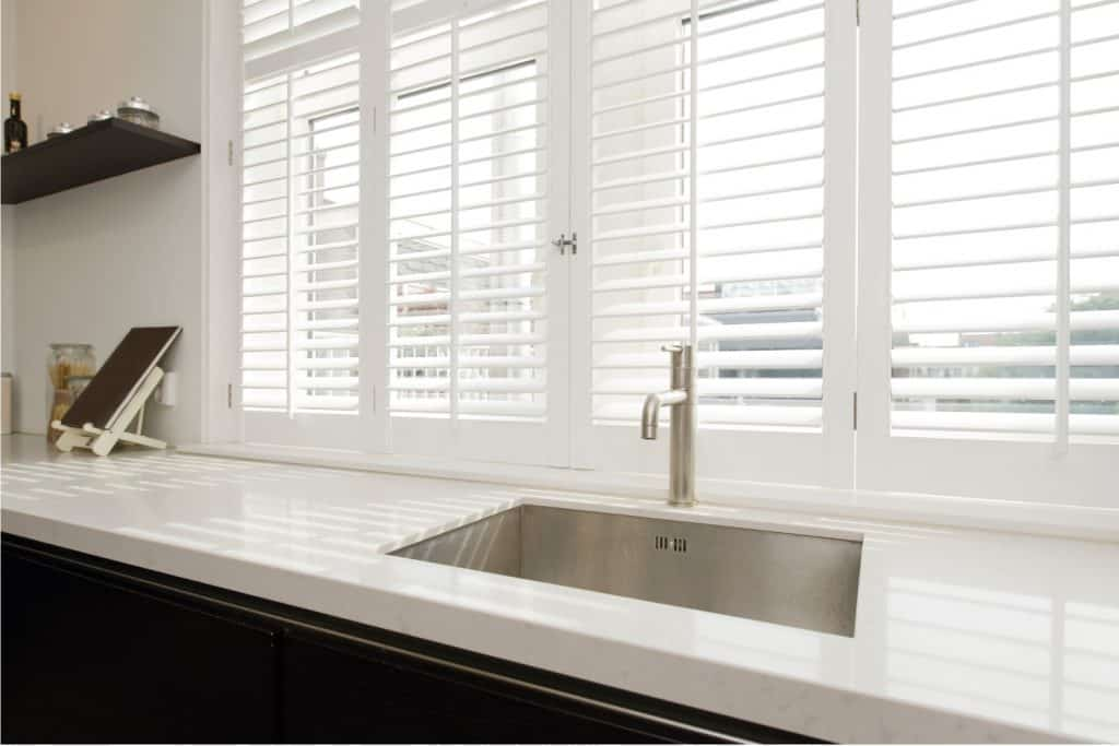 Modern kitchen with white countertop and plantation shutters on windows