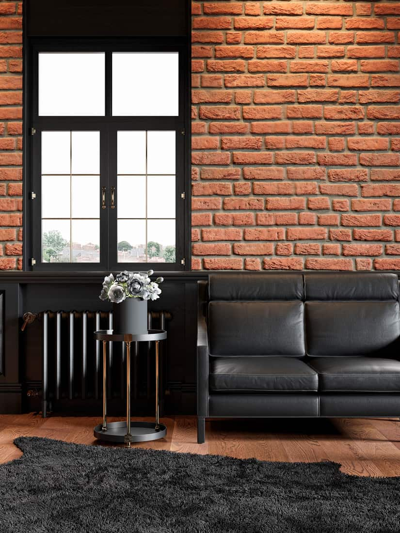 oft interior with brickwall, leather couch, wood panel, window and carpet.