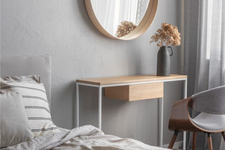 Elegant round mirror in wooden frame above fancy console table with flowers in vase, What Size Should A Console Table Be - Length, Height, And Depth (Inc. Behind A Sofa)
