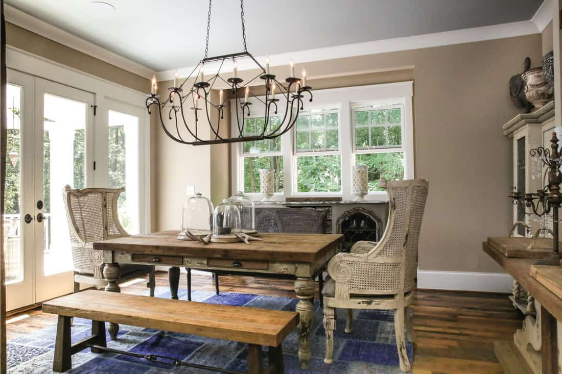 Shabby chic beautiful furniture of dining room with large heavy wooden dining table and chairs
