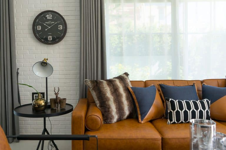 side table lamp and brown leather sofa with pattern cushions in industrial style decoration, Does Leather Furniture Stretch And Sag?