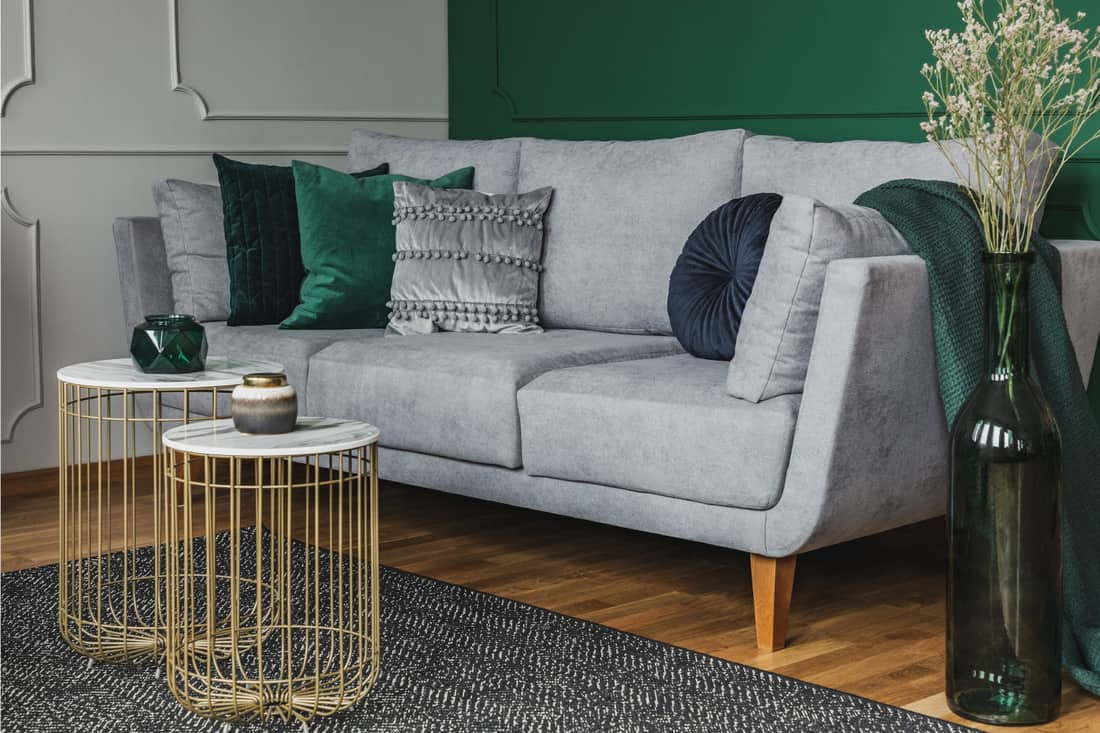 Small coffee tables with marble tops and gold in front of elegant gray couch with emerald green pillows