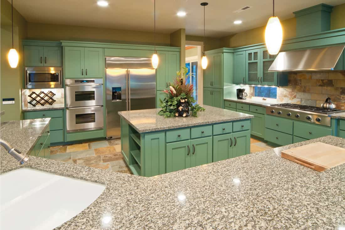 Teal kitchen interior with marble countertop