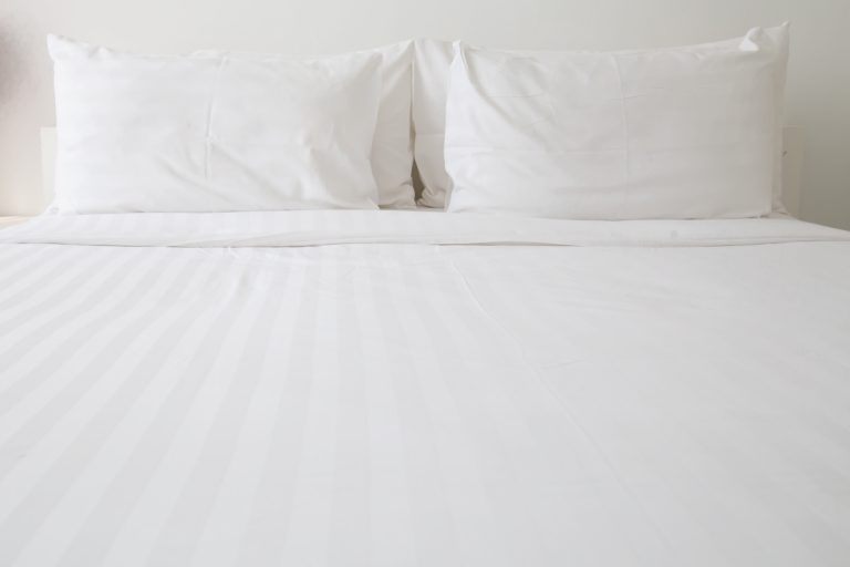 White flannel sheets and white pillows in bed, How To Wash And Soften Flannel Sheets To Keep From Pilling