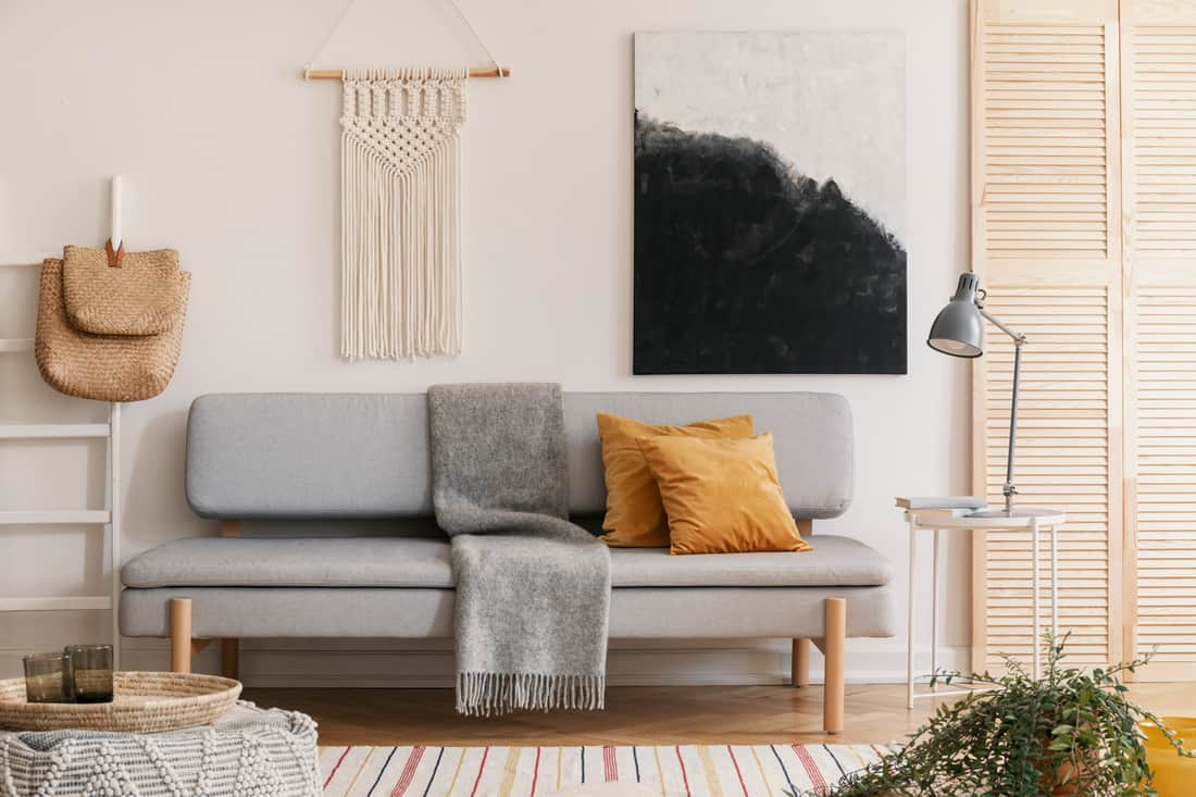 white wall of natural living room interior with grey fashionable couch with yellow pillow and warm blanket