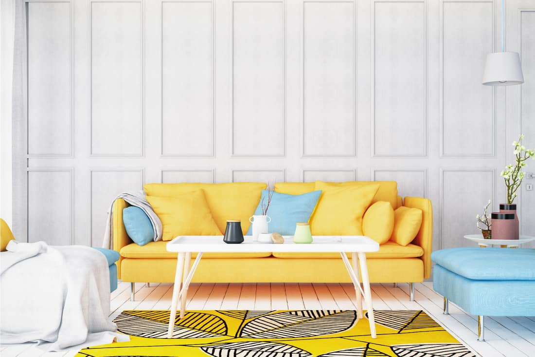 White walled living room with bright yellow sofa and white rectangular coffee table on yellow carpet with black leaves design