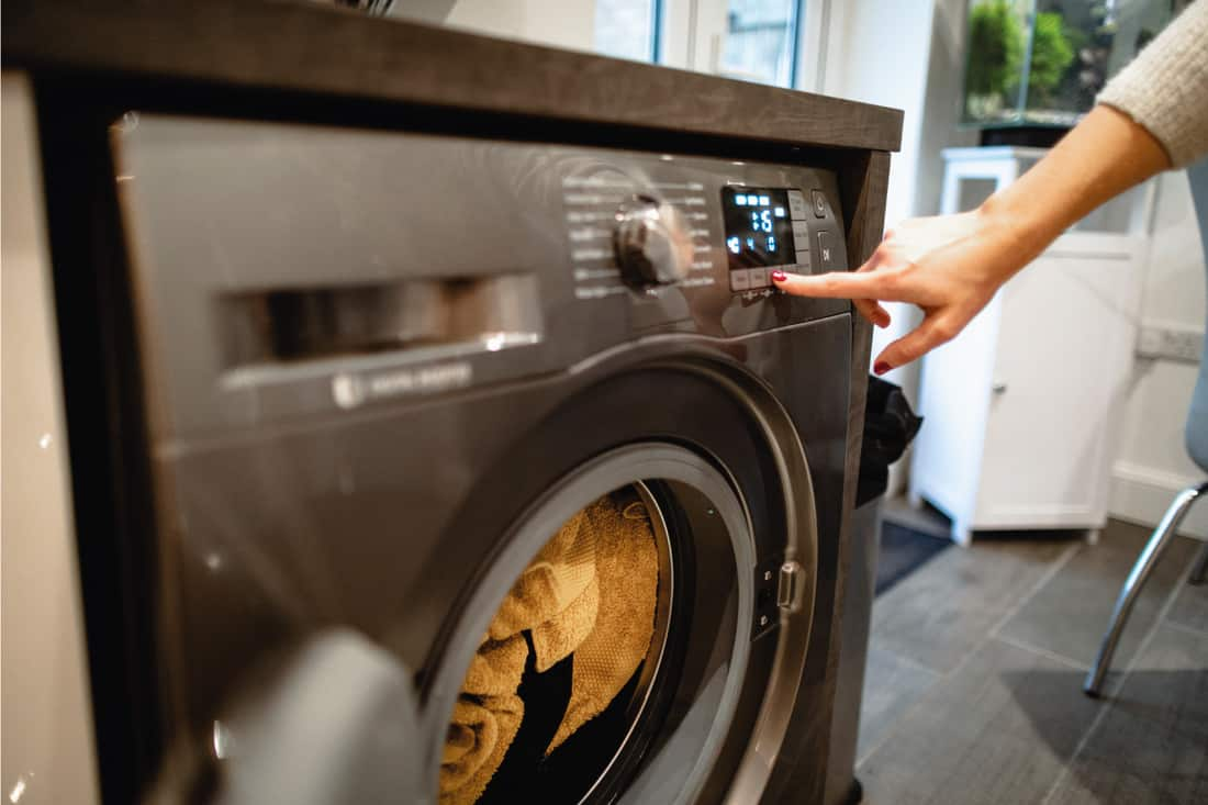 Woman pressing a button on her washing machine, setting the machine cycle