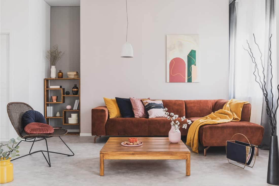 Wooden coffee table in fashionable living room interior with brown corner sofa and perfectly sized bookshelf on the living room corner