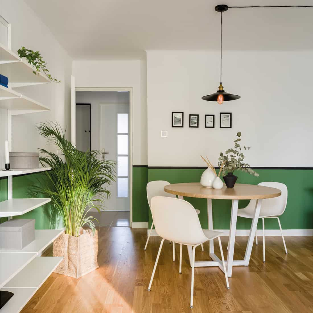Wooden dining table, white and green walls, wooden floor, and chair rail molding