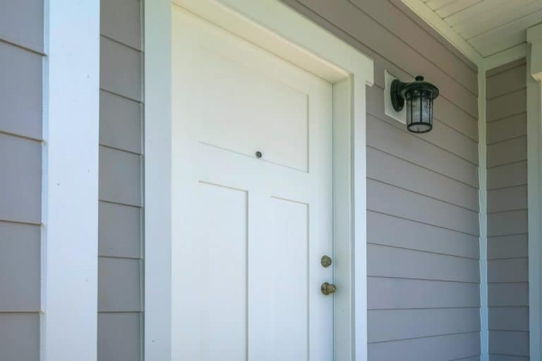 Wooden door and wooden siding of a modern home, How Long Does Wood Siding Last?