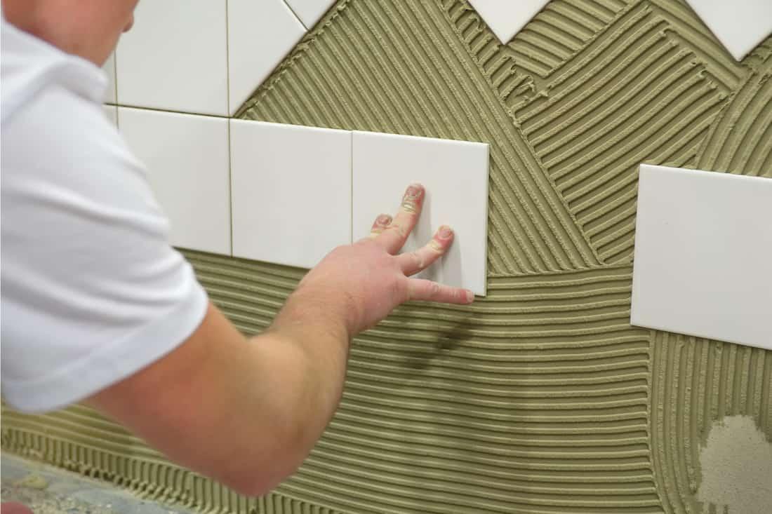 Worker using tile glue installing white wall tiles