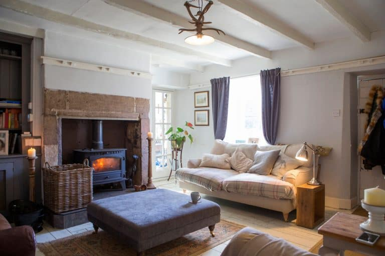 A beautiful photo of a cosy living room with fireplace, Should Furniture Face The Fireplace?