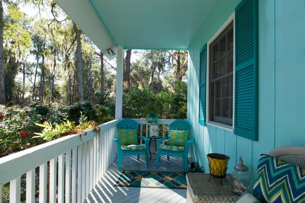 A blue colored porch with blue wooden chairs, blue throw pillows, and a white colored fence