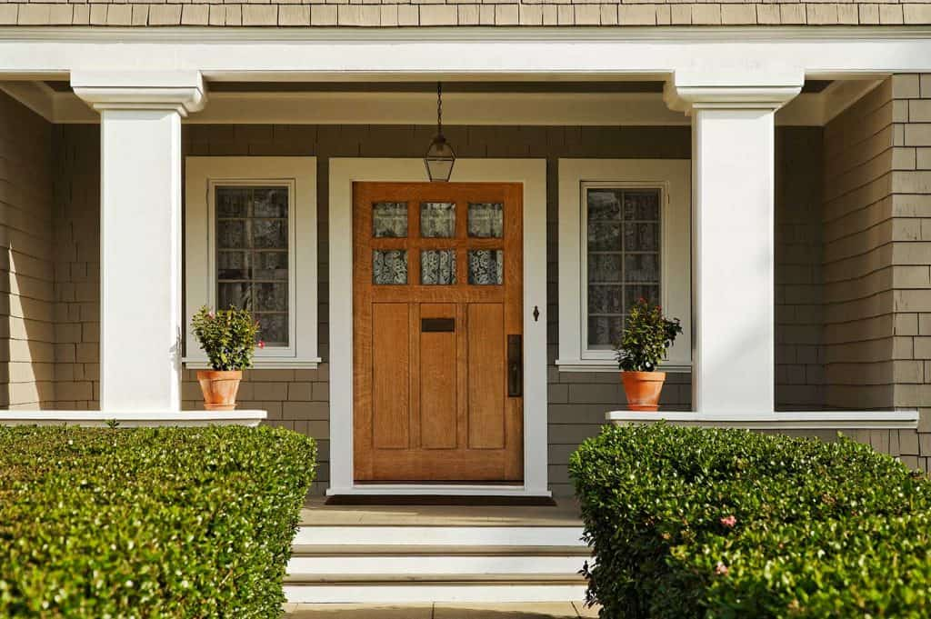 A concrete walkway bordered with hedged shrubs leads to the front door of a home