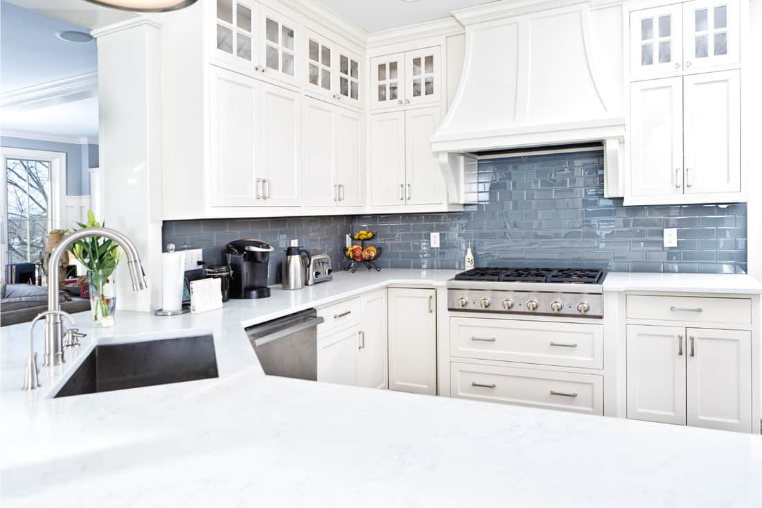 A contemporary home kitchen with stainless steel appliances and painted white cabinets. with silver knobs