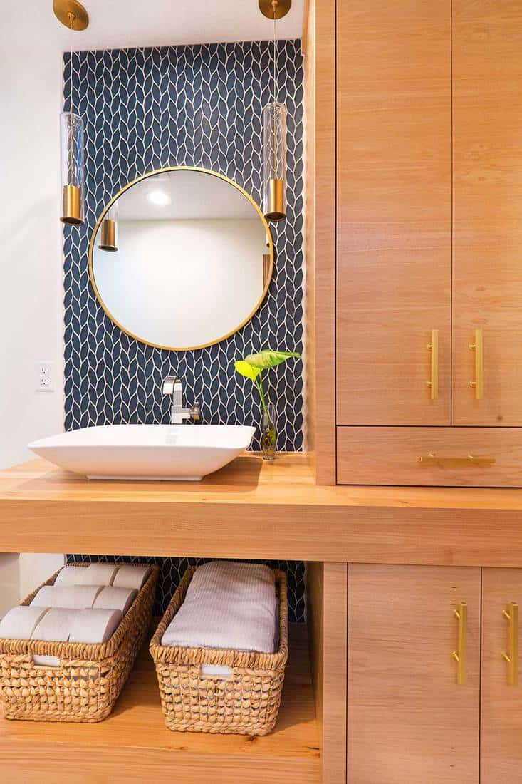 A contemporary modern bathroom design featuring a round mirror, an above counter vessel sink and a custom built vanity with storage