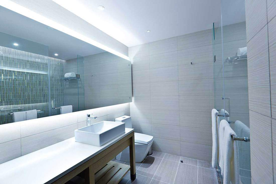 A contemporary modern bathroom design, glass enclosed shower stall, vanity and sink counter