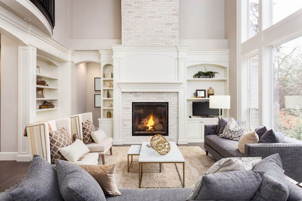 A cozy and warm white living room with gray sectional sofas, beige carpet, and a ceramic center console table