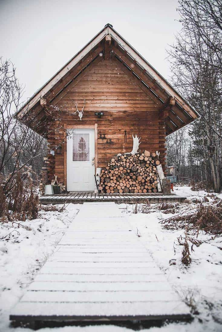 A cozy log cabin in the forest at winter time with lots of snow around