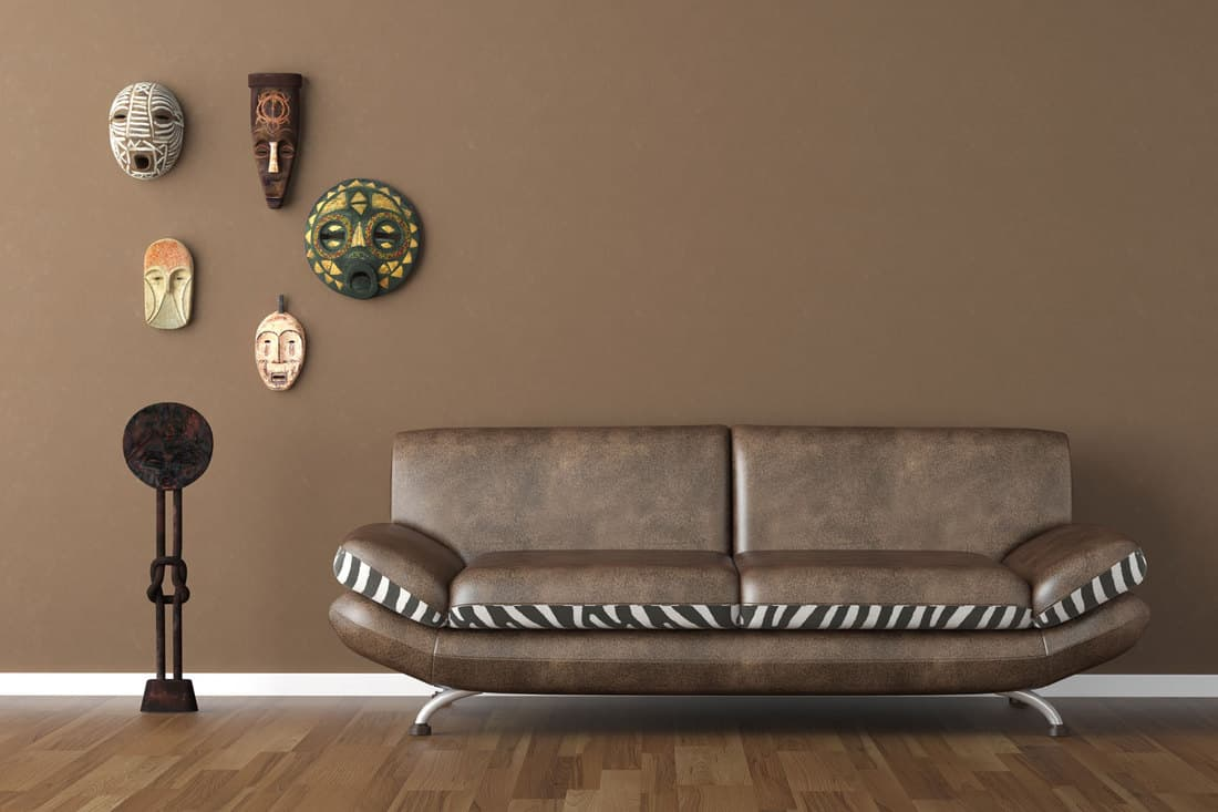 A dark brown colored living room with a dark leather sofa