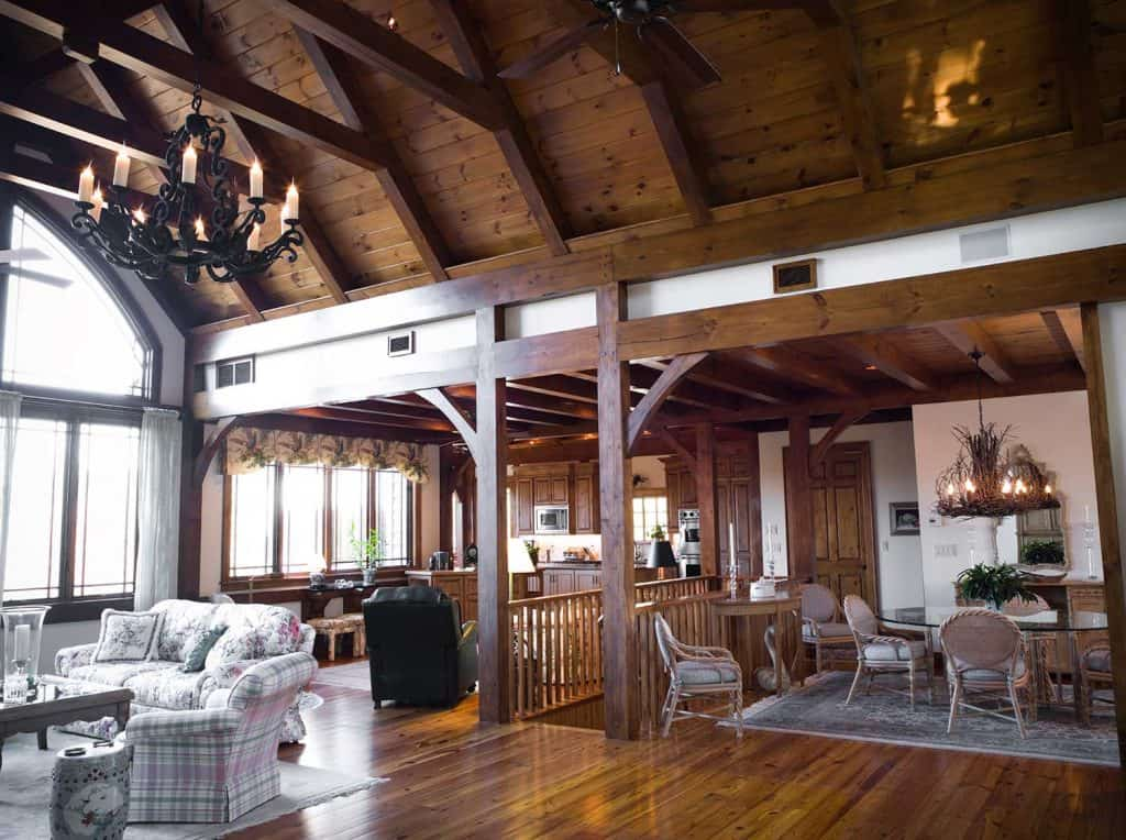 A den or living room with a beautiful stone fireplace and wooden beams