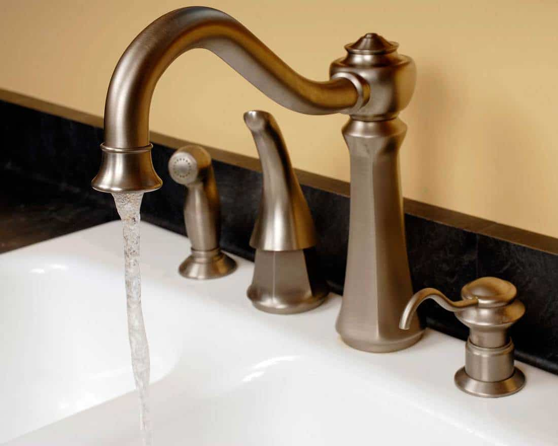 A faucet with running water by a sink in a modern kitchen