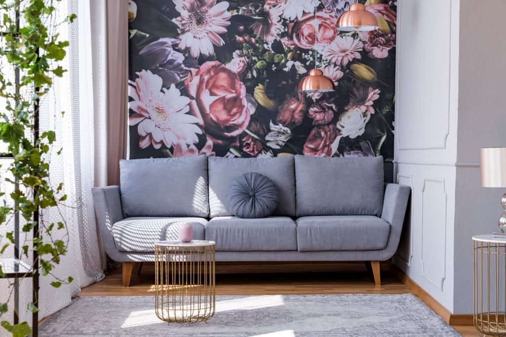 A floral themed living room nook with a gray sofa, cool minimalist inspired coffee table, and a gray carpet