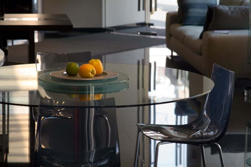 A glass dining table with a black curved dining chair