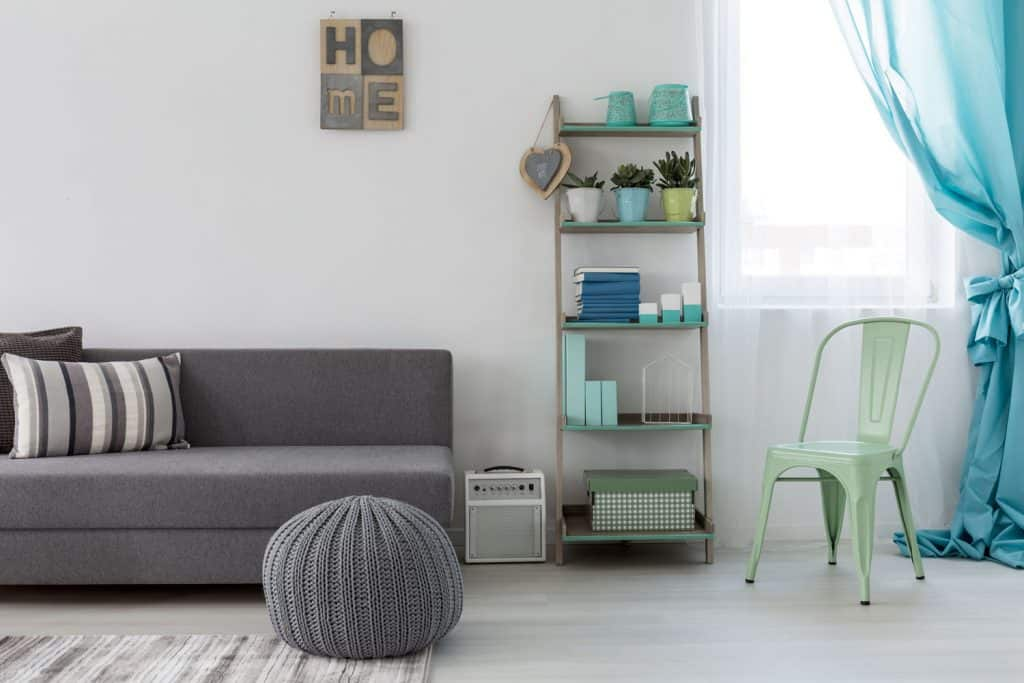 A gorgeous blue-gray themed living room with a gray ottoman