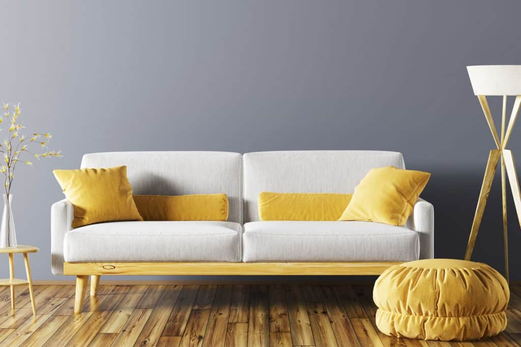 A gorgeous brightly colored living room with a hardwood flooring, white loveseat sofa with yellow throw pillows, and a gray colored wall