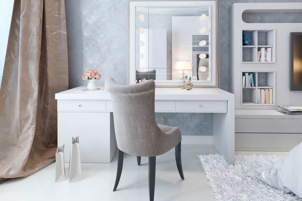 A gorgeous modern dressing table wiht cloth and a cement pattern wallpaper with bookshelves on the side