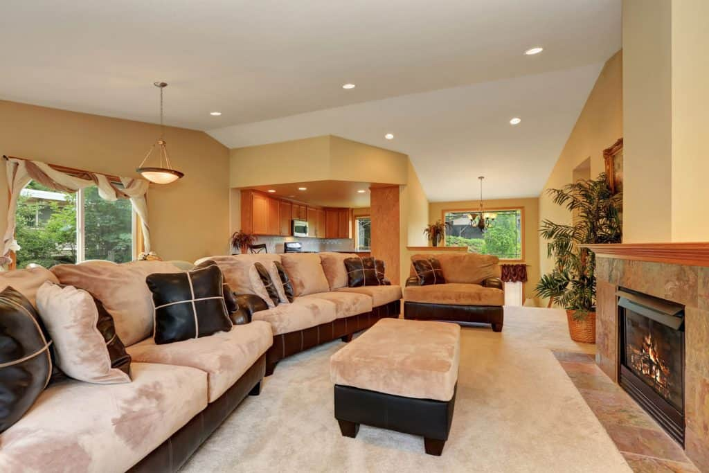 A gorgeous tan colored living room with suede fabric chairs, sofas, and ottoman