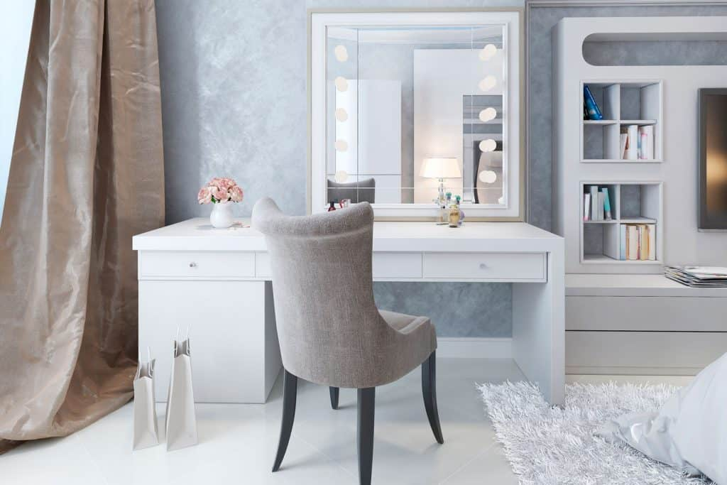 A gorgeous white and gray themed dresser with cloth accent chair