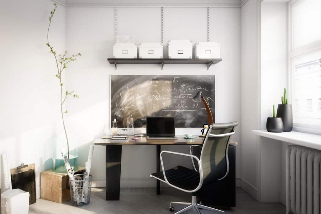 A gorgeous work area with a white painted wall, modern standing desk, and a comfortable working chair
